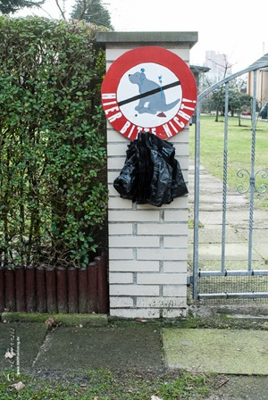 Ein Grundstücksbesitzer möchte keine Hundehaufen unter seiner Hecke, also hängt er Gassibeutel auf.