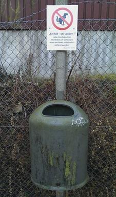 Im Kleingarten: Ein Mülleimer mit Hinweisschild, dass Hundebesitzer die Haufen ihrer Vierbeiner bitte hier hinein entsorgen mögen.