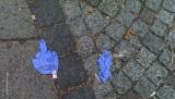 Weg geworfener Einmalhandschuh zeigt uns den MittelfingerMittelfinger